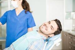 Het glimlachen Mensenzitting door Tandarts At Clinic stock foto's