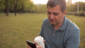 Het glimlachen mensenzitting op het gazon in het Park met een koffiedrank en een telefoon en het spreken aan een vriend stock videobeelden