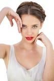 Het glimlachen model in het witte kleding stellen wat betreft haar tempel en haar Stock Foto's