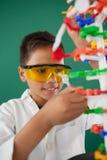 Het glimlachen model van de schooljongen het experimenterende molecule in laboratorium Royalty-vrije Stock Afbeelding