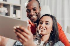 Het glimlachen monogame verbintenis aan elkaar en het gebruiken van tablet stock afbeeldingen