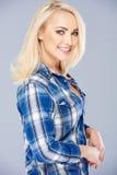 Het glimlachen mooie blond in een gecontroleerd blauw overhemd Royalty-vrije Stock Foto