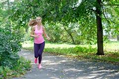 Het glimlachen mooie sportieve vrouwenjogging in Park bij de zomer royalty-vrije stock afbeeldingen