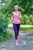 Het glimlachen mooie sportieve vrouwenjogging in Park bij de zomer stock fotografie