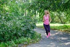 Het glimlachen mooie sportieve vrouwenjogging in Park bij de zomer royalty-vrije stock foto's