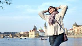Het glimlachen het mooie vrouw stellen op dijk met mening bij de historische bouw en het watervervoer stock footage