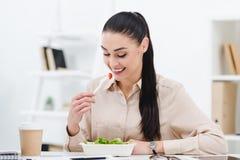 het glimlachen onderneemster het eten haalt salade voor lunch weg stock afbeelding