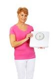 Het glimlachen oude het gewichtsschaal van de vrouwenholding Royalty-vrije Stock Foto
