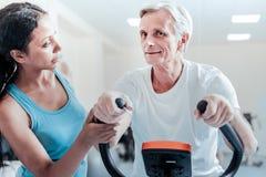Het glimlachen oude man opleiding en een ernstige vrouw dichtbij hem stock foto