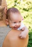 Het glimlachen over de Schouder van het Mamma `s Royalty-vrije Stock Afbeeldingen