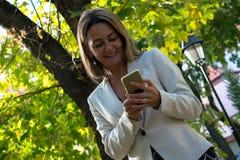 Het glimlachen het overseinen van de onderneemstertekst op celtelefoon in aard stock foto