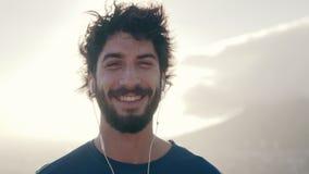 Het glimlachen portret van een mannelijke atleet tegen zonlicht stock footage