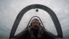 Het glimlachen proefzitting in de cockpit van een licht aerobatic vliegtuig, emoties van de vlucht, kunstvliegen stock footage