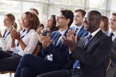 Het glimlachen publiek het toejuichen bij een bedrijfsseminarie royalty-vrije stock foto