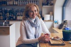 Het glimlachen het rijpe vrouw stellen bij camera in koffie Stock Foto