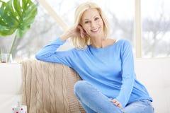 Het glimlachen rijpe vrouwenzitting op bank thuis royalty-vrije stock fotografie