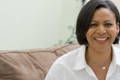 Het glimlachen rijpe vrouwenzitting op haar bank Royalty-vrije Stock Foto's