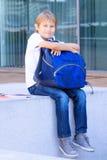 Het glimlachen schooljongenzitting met zijn rugzak openlucht Onderwijs, terug naar school, reisconcept Royalty-vrije Stock Afbeeldingen