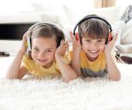 Het glimlachen siblings het luisteren muziek met hoofdtelefoons Stock Afbeeldingen
