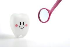 Het glimlachen tandenstuk speelgoed emotie met tandspiegel op witte achtergrond stock foto's