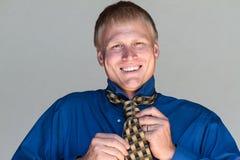 Het glimlachen terwijl het binden van zijn stropdas Royalty-vrije Stock Afbeeldingen
