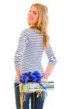 Het glimlachen tienermeisje verbergen huidig achter rug Stock Fotografie