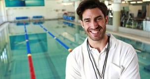 Het glimlachen trainer het stellen door de pool stock video