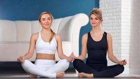 Het glimlachen twee het aanbiddelijke vrouw het praktizeren de lotusbloempositie van de yogazitting stellen die camera bekijken stock video