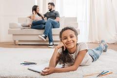 Het glimlachen van Afrikaanse Amerikaanse meisjestekening met potloden terwijl thuis het liggen op tapijt Royalty-vrije Stock Fotografie
