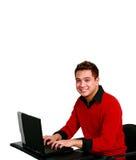 Het glimlachen van Aziatische kerel op computer stock afbeeldingen