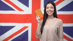 Het glimlachen van het Aziatische paspoort van de meisjesholding tegen Britse vlagachtergrond, burgerschap stock videobeelden
