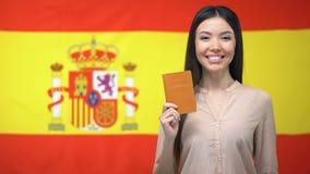Het glimlachen van het Aziatische paspoort van de meisjesholding tegen Spaanse vlagachtergrond, burgerschap stock video