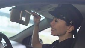 Het glimlachen van Aziatische politiedame het aanpassen hoed op bestuurderszetel in patrouillevoertuig, plicht stock footage