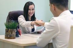 Het glimlachen van het bedrijfsvrouw schudden handen met een jonge bedrijfsman bij Bureau in bureau Het concept het gesprek, over stock afbeeldingen