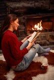 Het glimlachen van het boek van de meisjeslezing voor open haard Royalty-vrije Stock Foto's