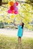 Het glimlachen van de ballons van de meisjesholding in het park Stock Foto