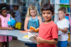 Het glimlachen van de boeken van de jongensholding tegen klasgenoten royalty-vrije stock fotografie
