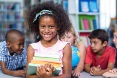 Het glimlachen van de boeken van de meisjesholding tegen klasgenoten royalty-vrije stock fotografie