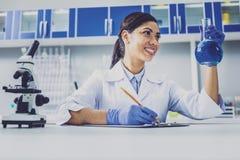 Het glimlachen van de donker-haired bol van de chemicusholding met blauwe vloeistof stock foto