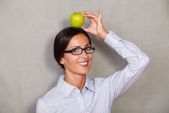 Het glimlachen van de donkerbruine appel van de dameholding op hoofd Royalty-vrije Stock Foto's