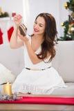 Het glimlachen van de donkerbruine schoenen van de holdingsbaby bij Kerstmis Stock Foto's
