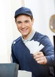 Het glimlachen van de Kaartjes van de Arbeidersholding op Bespreekbureau royalty-vrije stock foto