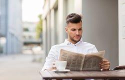 Het glimlachen van de krant van de mensenlezing bij de koffie van de stadsstraat Stock Fotografie