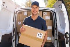 Het glimlachen van de ladingsdozen van de leveringsmens in zijn vrachtwagen stock fotografie