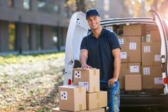 Het glimlachen van de ladingsdozen van de leveringsmens in zijn vrachtwagen royalty-vrije stock afbeelding