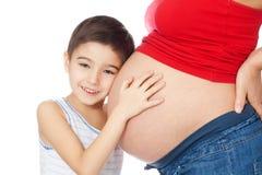 Het glimlachen van de moederbuik van de jongensholding met handen Stock Foto's