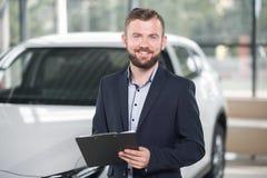 Het glimlachen van de omslag van de managerholding in autotoonzaal stock foto