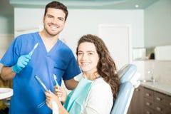 Het glimlachen van de Tandenborstels van Tandartsand woman holding in Tandkliniek stock fotografie