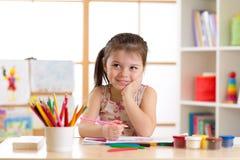 Het glimlachen van de tekening van het jong geitjemeisje met kleurenpotloden in opvangcentrum royalty-vrije stock fotografie