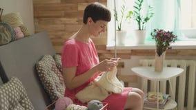 Het glimlachen van de wollen kleren van vrouwenbreinaalden op achtergrondvenster stock videobeelden